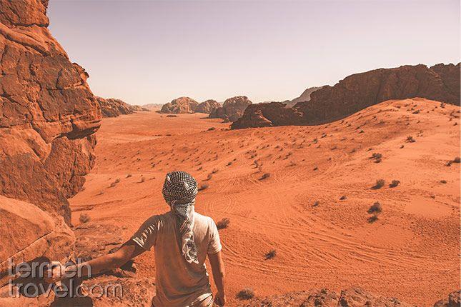 Kaluts, Kerman. Man standing on Kaluts, looking over the vast dry orange desert.