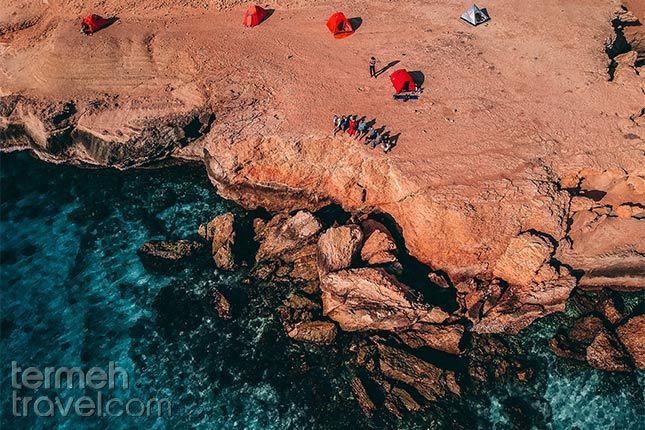 Qeshm, Iran. Helishot of a group of travelers on the edge of a rocky beach looking onto the Persian Gulf.