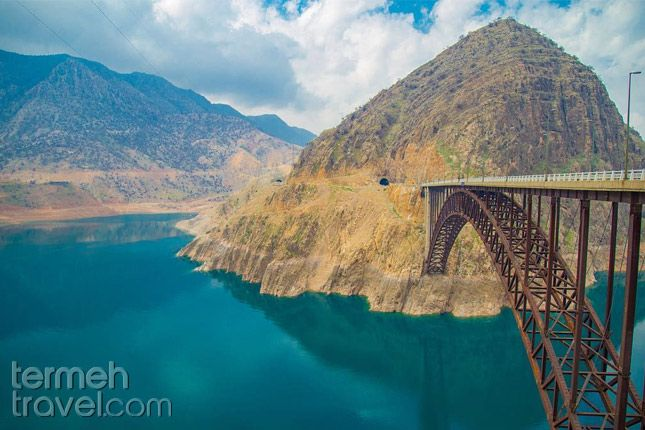 Dez Dam, Dezful, Iran. Blue waters and blue skies flowing through tree-covered mountains.