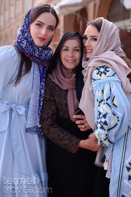 tourists in Iran posing with local woman wearing Chador in Isfahan