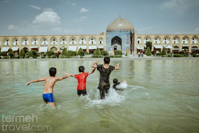 Isfahan, Iran. Kids in Naqshe Jahan Square, running through the pool in the heat of summer.