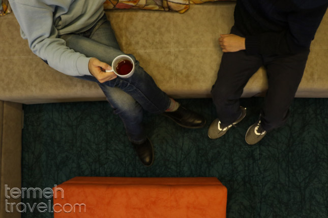 two people enjoying tea with shoes on, on a carpet - Termeh Travel