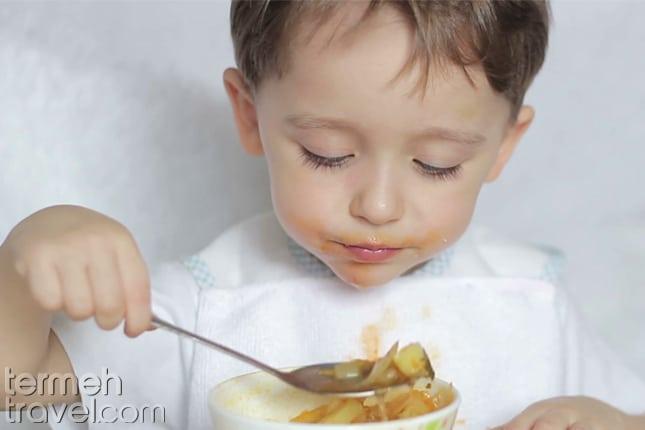 A kid eating Eshkeneh- Termeh Travel
