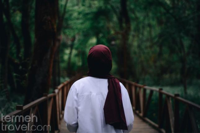 Solo female traveller standing on a wooden bridge- Termeh Travel