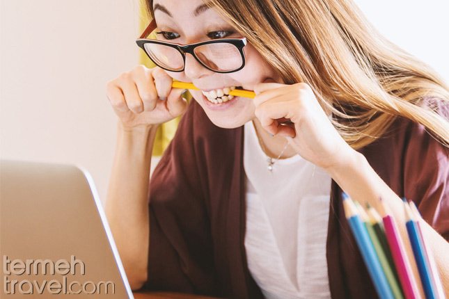 A girl biting her pencil out of stress while writing- Termeh Travel