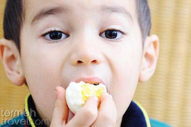 A kid eating boiled egg
